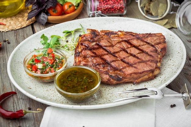 Ossenhaas steak op plaat met saus, op een houten tafel Premium Foto