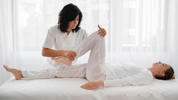 Osteopaat die een jonge vrouw behandelt in het ziekenhuis Gratis Foto