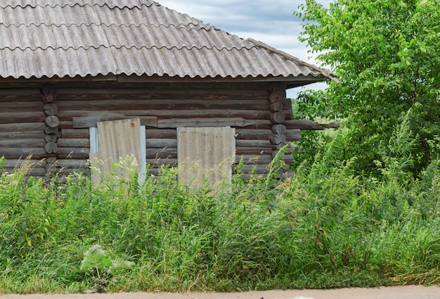 Oud blokhuis dat met lang gras wordt overwoekerd. verlaten landhuis. landelijke scène. Premium Foto