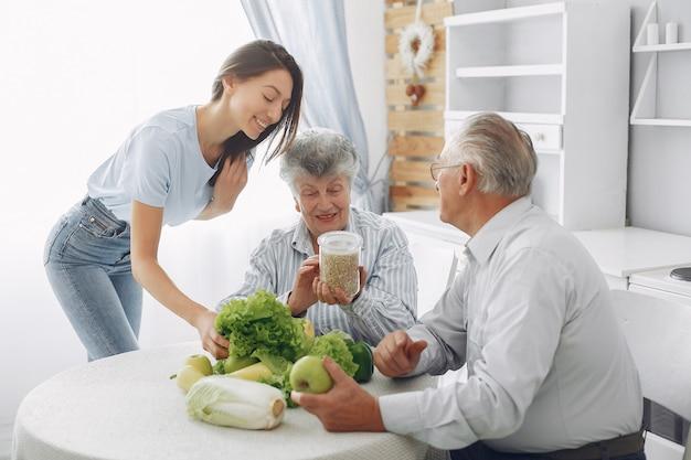 Oud echtpaar in een keuken met jonge kleindochter Gratis Foto