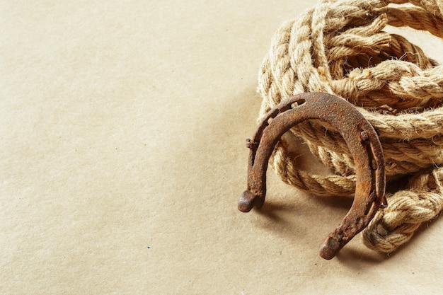 Oud hoefijzer en touw op houten planken Premium Foto