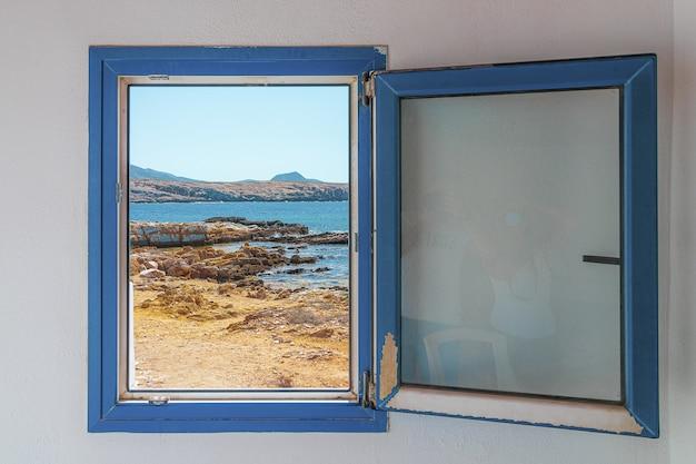 Oud houten blauw raam met uitzicht op het strand Gratis Foto