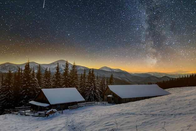Oud houten huis, hut en schuur, stapel brandhout in diepe sneeuw op bergvallei, net bos, bosrijke heuvels op donkere sterrenhemel en melkweg. berg winter nacht landschap. Premium Foto