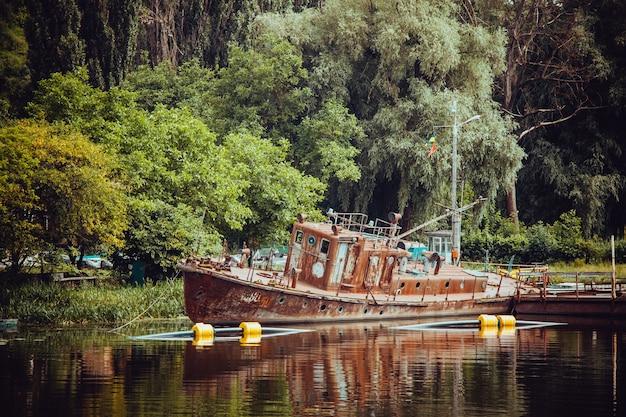 Oud houten schip dichtbij de oever van een meer, omgeven door weelderige natuur Gratis Foto