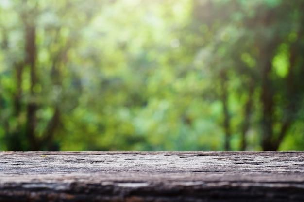 Oud houten tafelblad op groene vage abstracte achtergrond van gebladerteachtergrond. ready heeft ons producten voor display- of montageproducten gebruikt Premium Foto