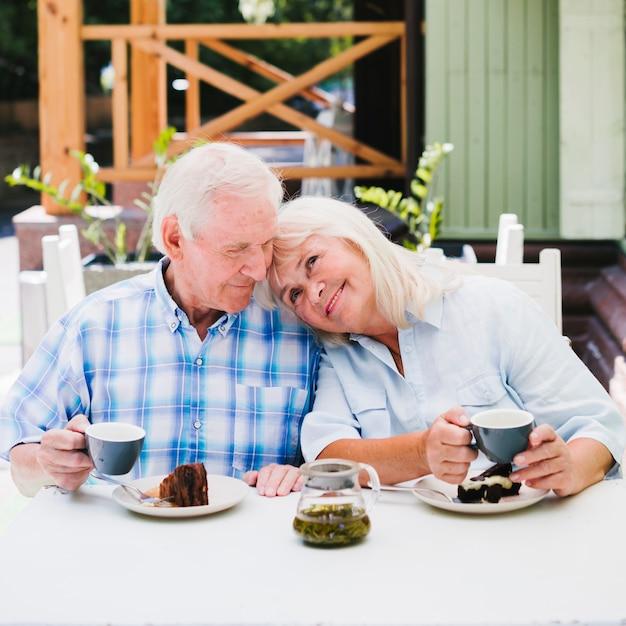 Oud paar dat van tijd geniet die samen in openlucht thee drinkt Gratis Foto