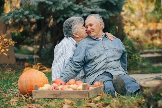 Oud paar sittingin een zomertuin met oogst Gratis Foto