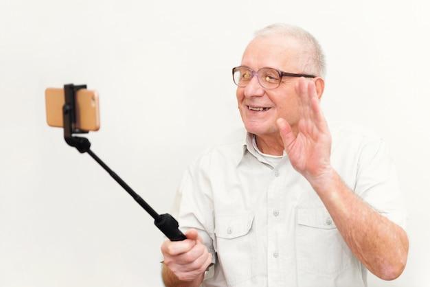 Oude actieve mens die selfie met mobiele die telefoon nemen op grijs achtergrond vlogger blogger concept wordt geïsoleerd Premium Foto