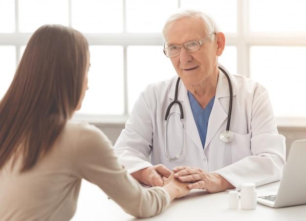 Oude arts in witte medische jas en bril. Premium Foto