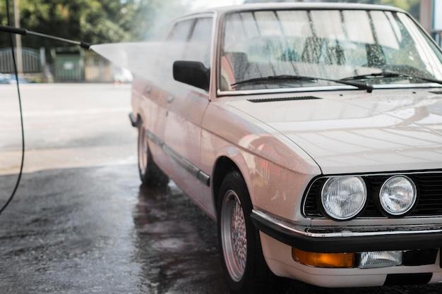 Oude auto die met waterslang wordt gewassen Premium Foto