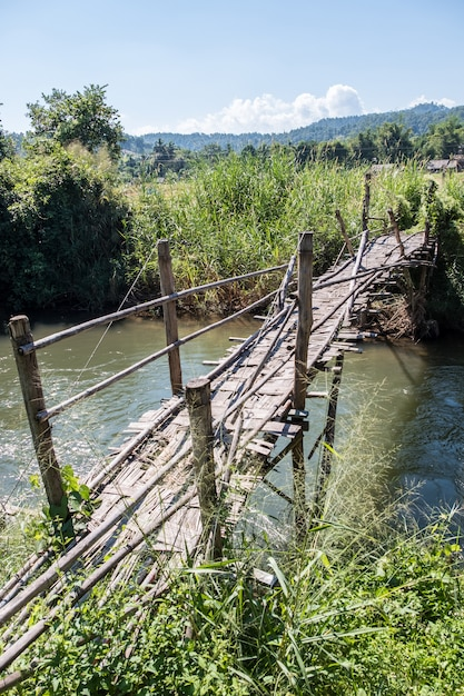 Oude bamboe brug steekt de kleine rivier over. Premium Foto