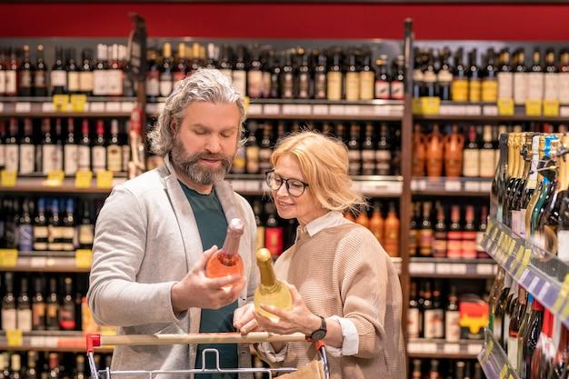 Oude bebaarde man met fles rose wijn en zijn blonde vrouw lezen van informatie op etiket tijdens het kiezen van alcoholische dranken Premium Foto