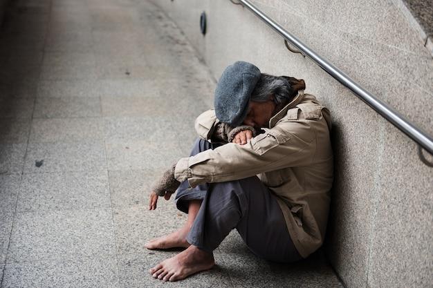 Oude bedelaar of dakloze vuile man zonder schoenen die en op gang zitten slapen Premium Foto