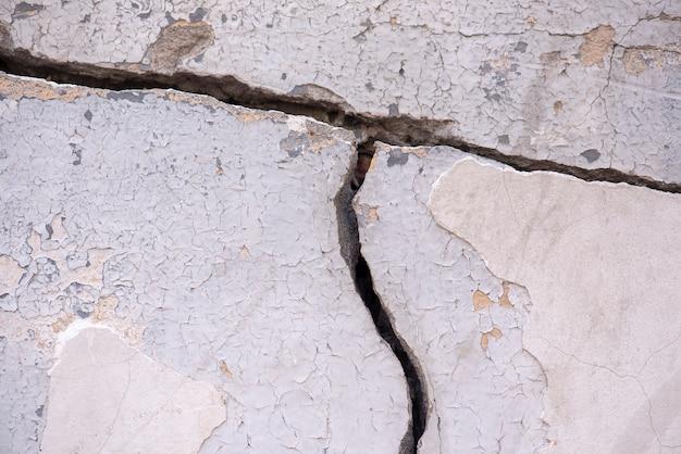 Oude betonnen muur met diepe grote scheur als achtergrond of textuur Premium Foto