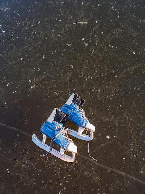 Oude blauwe schaatsen liggen op het ijs van een bevroren meer in de vroege zonnige ochtend in de winter Premium Foto