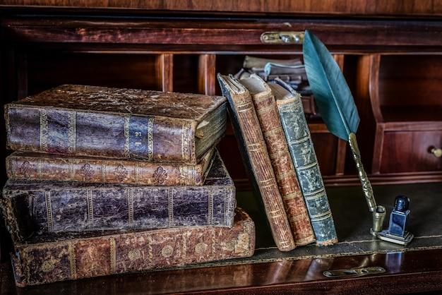 Oude boeken bij het schrijven van bureau en pen Premium Foto