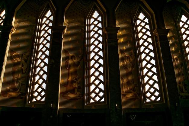 Oude christelijke tempel met middeleeuwse kunstwerken naast de ramen Gratis Foto
