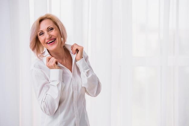 Oude dame met kort haar die gelukkig kijkt Gratis Foto