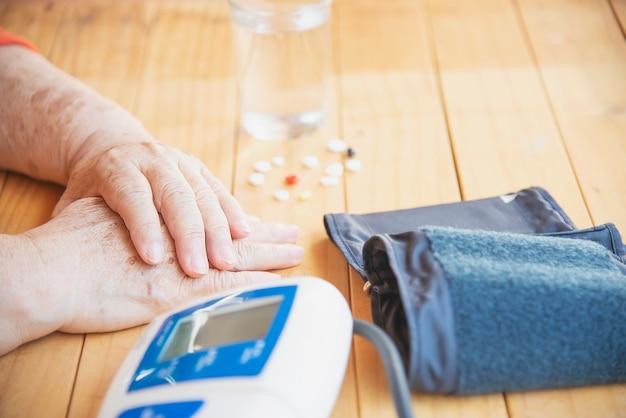 Oude dame wordt bloeddruk gecontroleerd met behulp van bloeddrukmeter kind ingesteld Gratis Foto