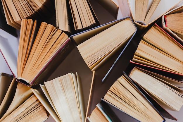 Oude en gebruikte hardcover boeken of schoolboeken zichtbaar van bovenaf. bovenaanzicht van open boeken op tafel. Premium Foto