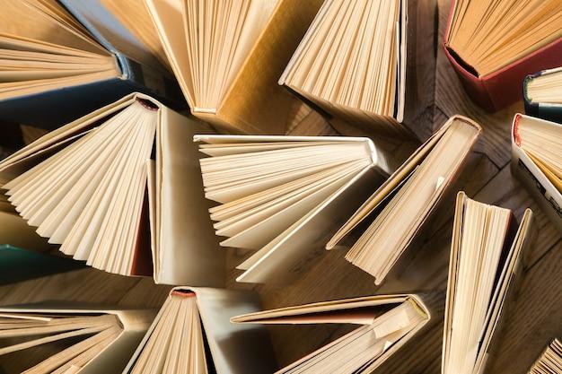 Oude en gebruikte hardcover boeken, tekstboeken van bovenaf gezien op een houten vloer. Premium Foto