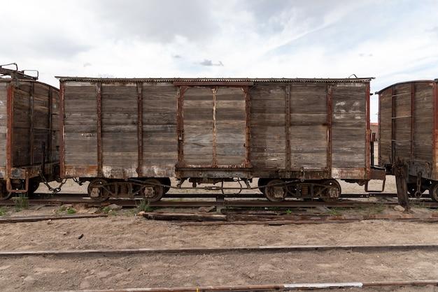 Oude en roestige houten treinauto achtergelaten op een spoorlijn. bolivia Premium Foto