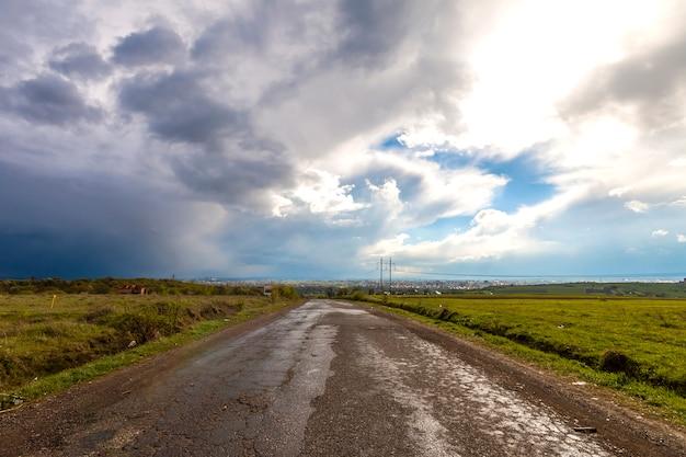 Oude gebarsten weg na regen. slechte hobbelige straat met gaten en stormachtige bewolkte hemel. Premium Foto