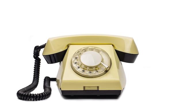 Oude gele telefoon op een witte achtergrond. blanco om te bewerken. Premium Foto