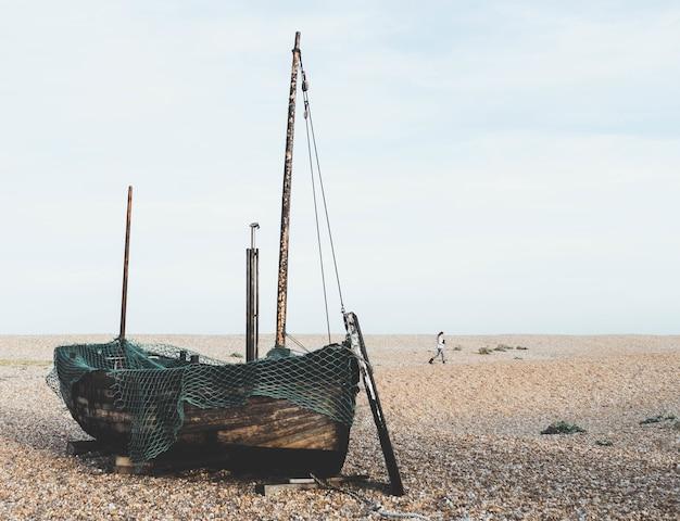 Oude houten boot op het zand achter een vrouw Gratis Foto