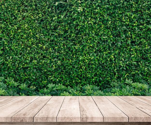 Oude houten plank met abstracte natuurlijke groene bladeren achtergrond voor productvertoning Premium Foto