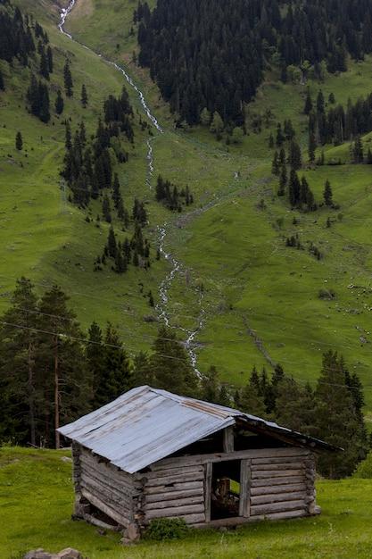Oude houten schuur omgeven door bossen en rotsen met de rivier Gratis Foto