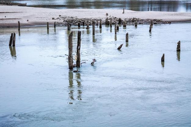 Oude houten stapels van oude verwoeste pier uit het water Premium Foto