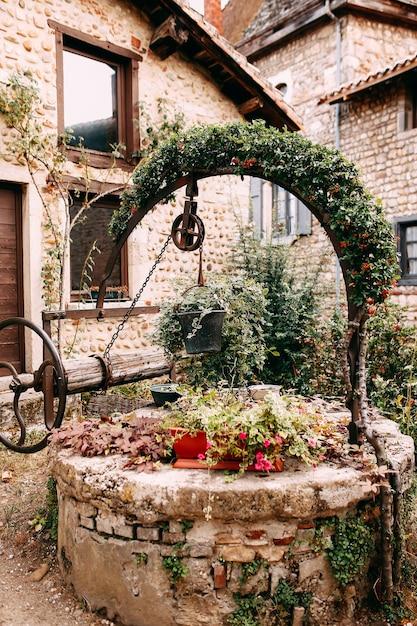 Oude houten steen goed met rode bloem boog en klimop in perouges, frankrijk. hoge kwaliteit foto Premium Foto