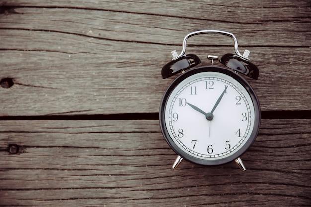 Oude klokplaats op houten achtergrond met ruimte voor tekst voor het concept van het tijdengeheugen. Premium Foto
