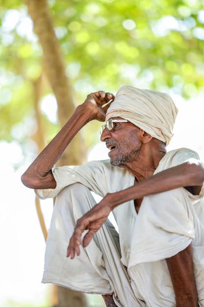 Oude landelijke indiase man zittend op de grond Premium Foto