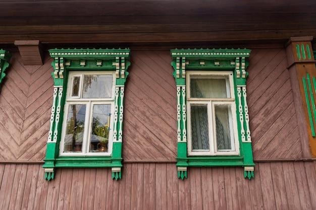 Oude lichte gevel van traditionele russische landelijke huis gemaakt van houten logboeken met schattige ingerichte platbands op ramen op platteland op mooie zomerdag. Premium Foto