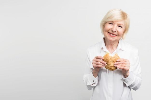 Oude maar tevreden vrouw houdt een hamburger in haar handen. ze heeft net een hap genomen. deze dame houdt van de smaak van deze maaltijd. soms eet ze graag junkfood. Premium Foto