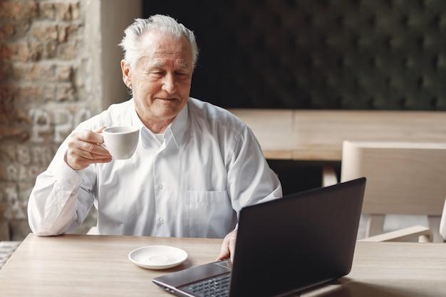 Oude man aan de tafel zitten en werken met een laptop Gratis Foto