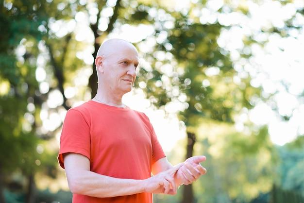 Oude man die de hartslag op zijn pols meet Premium Foto