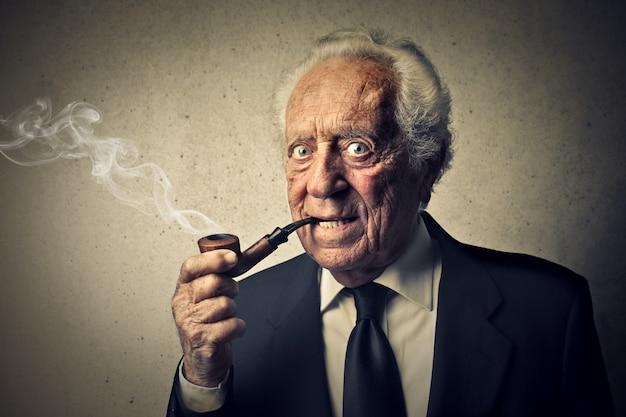 Oude man die een pijp rookt Premium Foto