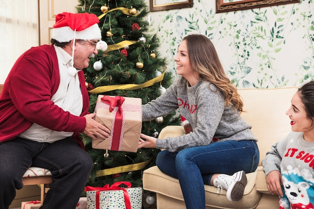 Oude man die giftdoos geeft aan jonge vrouw Gratis Foto