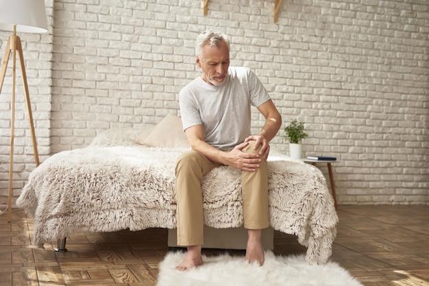 Oude man die lijden aan artritische kniepijn in slaapkamer. Premium Foto