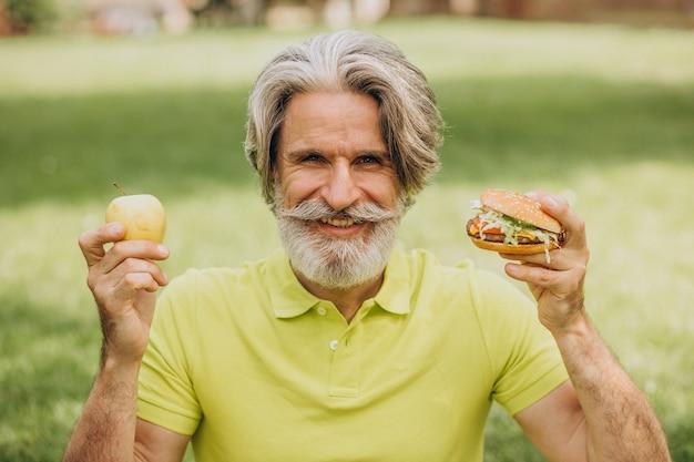 Oude man die tussen hamburger en appel kiest Gratis Foto