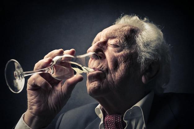 Oude man die wijn drinkt Premium Foto