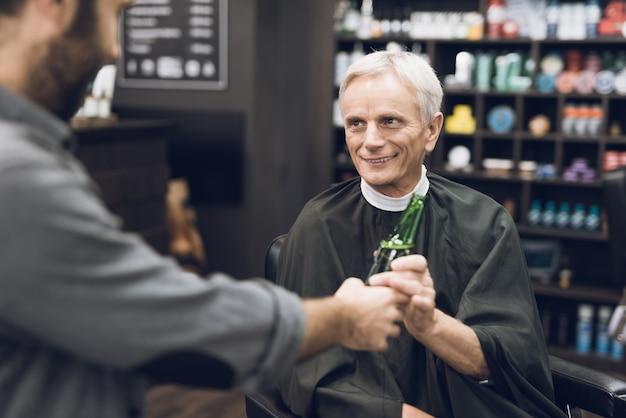 Oude man drinkt alcohol in de stoel van de kapper in kapperszaak, Premium Foto