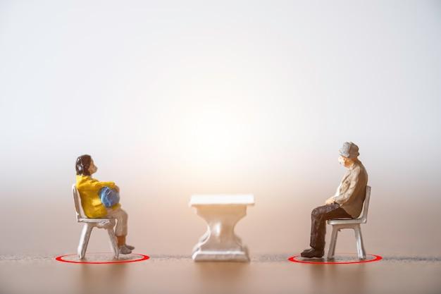 Oude man en vrouw miniatuurmensen die een gezichtsmasker dragen en op een stoel gaan zitten door afstand te houden bij het publiek om te voorkomen dat de covid-19-coronavirusuitbraak een pandemische infectie verspreidt. Premium Foto