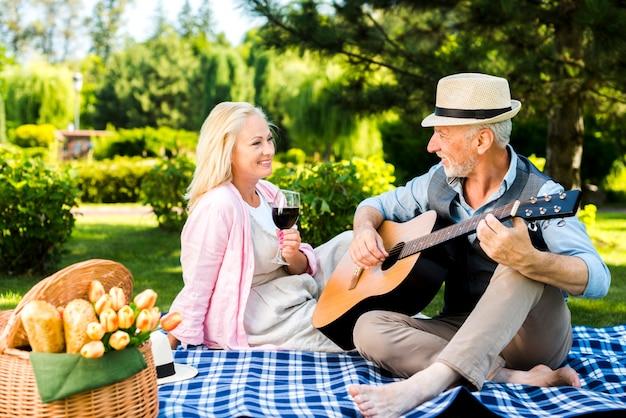 Oude man gitaar spelen voor zijn vrouw Gratis Foto