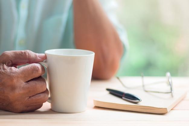 Oude man houdt witte kop koffie, wazig pen, laptop en glazen als achtergrond Premium Foto