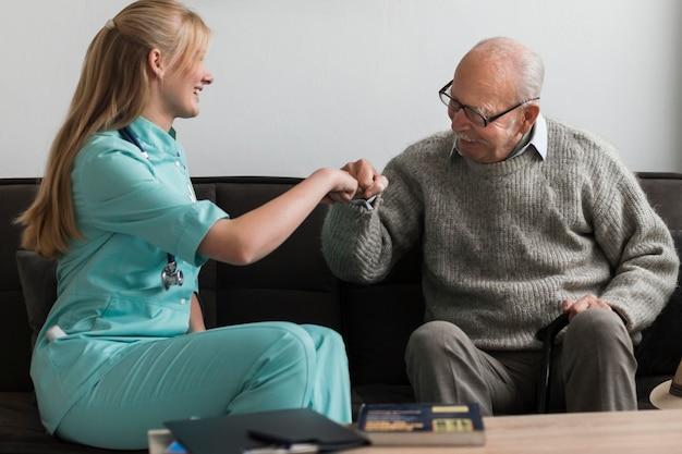 Oude man in een verpleeghuis vuist stoten verpleegster Gratis Foto