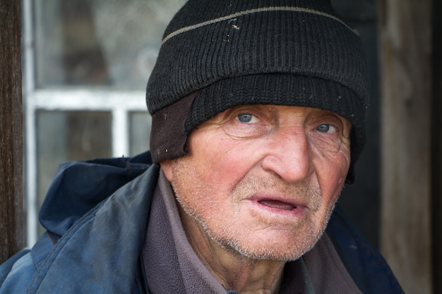 Oude man in slordige kleding staat op de drempel van zijn eigen verwoeste huis en kijkt in de verte Premium Foto